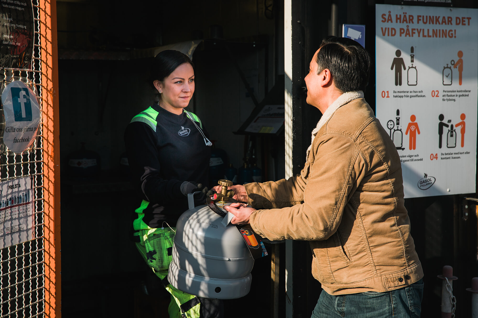 Kvinna ger en gasolflaska till en man