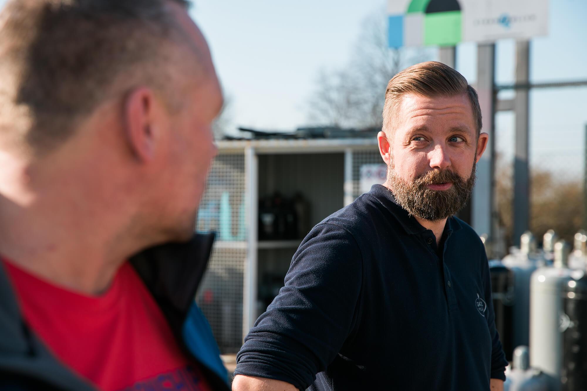 Två män pratar vid gasolfyllarnas station