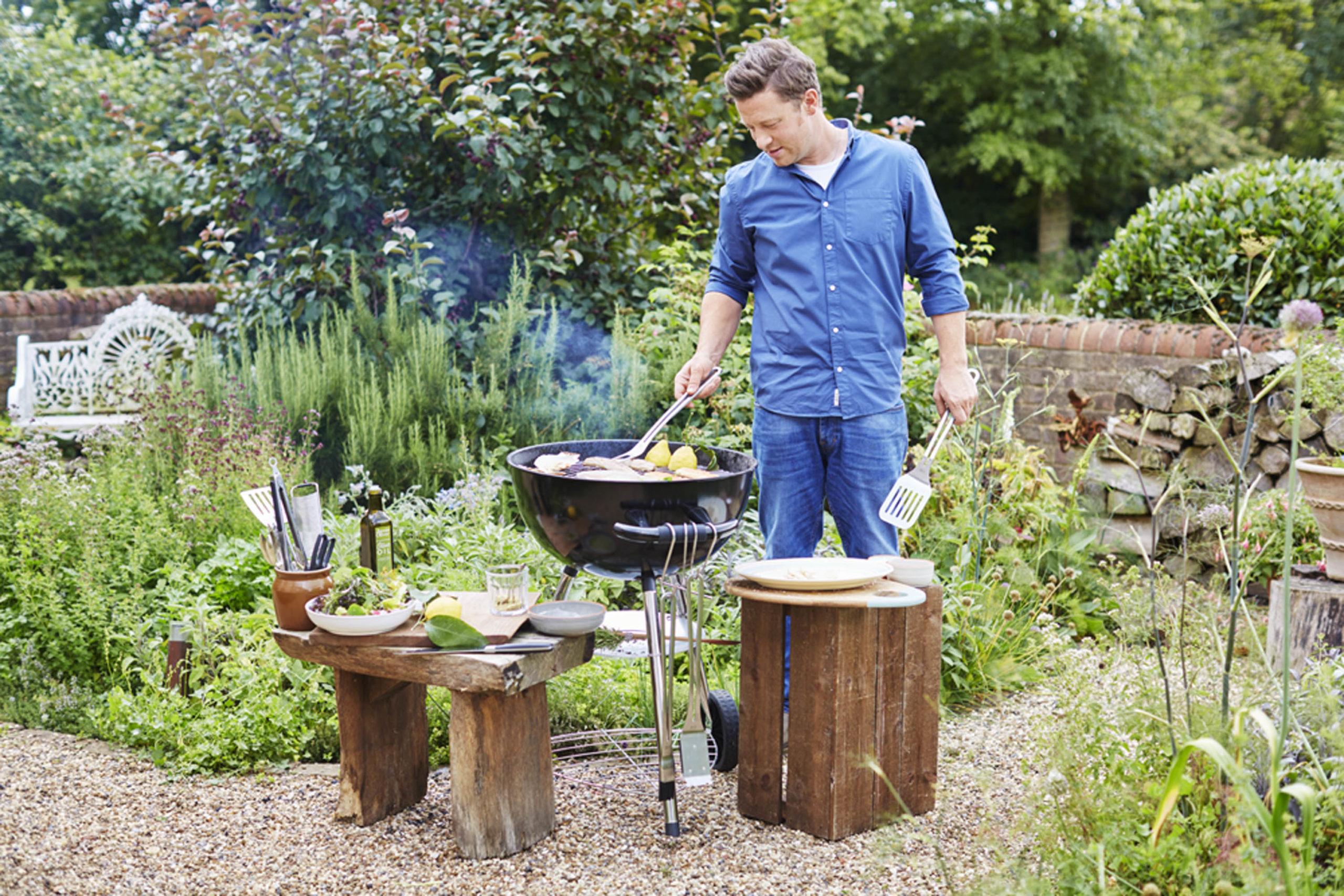 Man grillar i trädgården